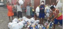 pessoas na rua recebendo alimentos e comemorando